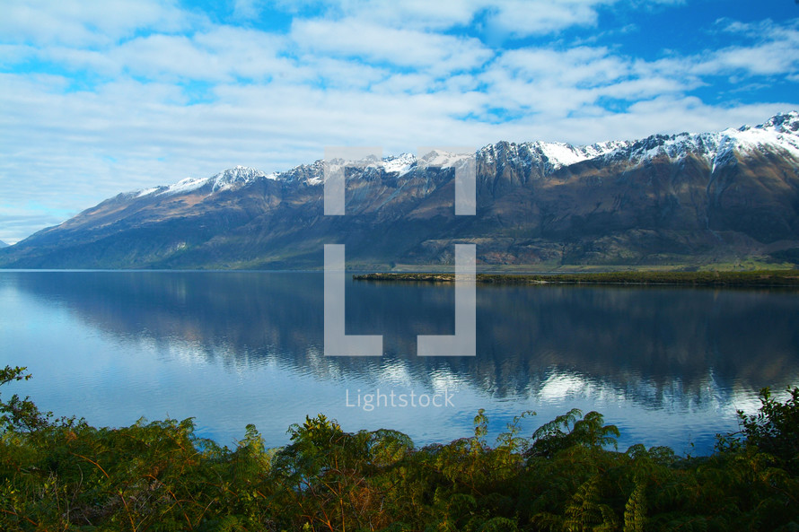 A range of snow capped mountains reflected in a clear lake