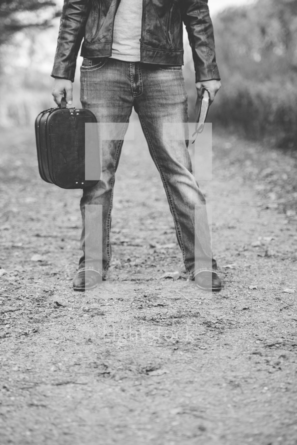 man holding a Bible and suitcase