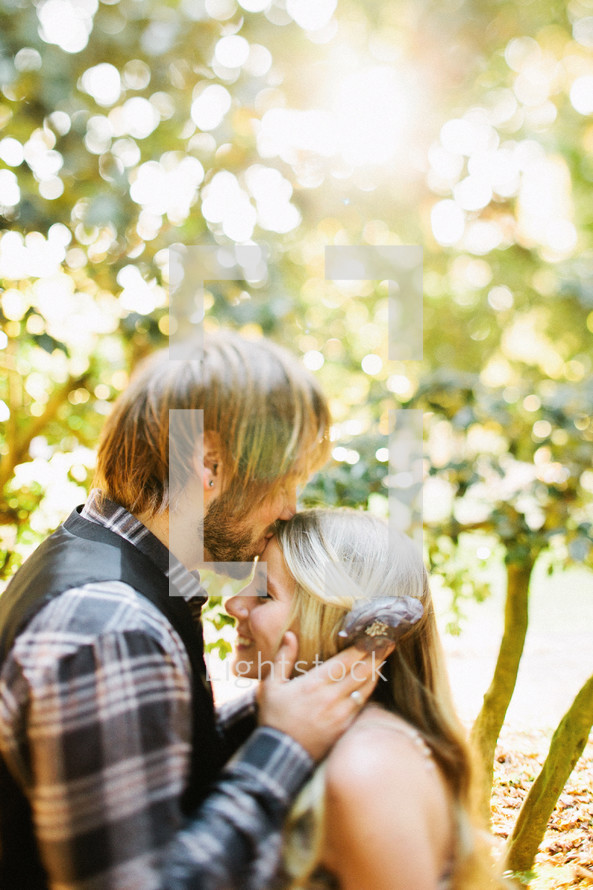 Man facing woman kissing her forehead with trees in background.