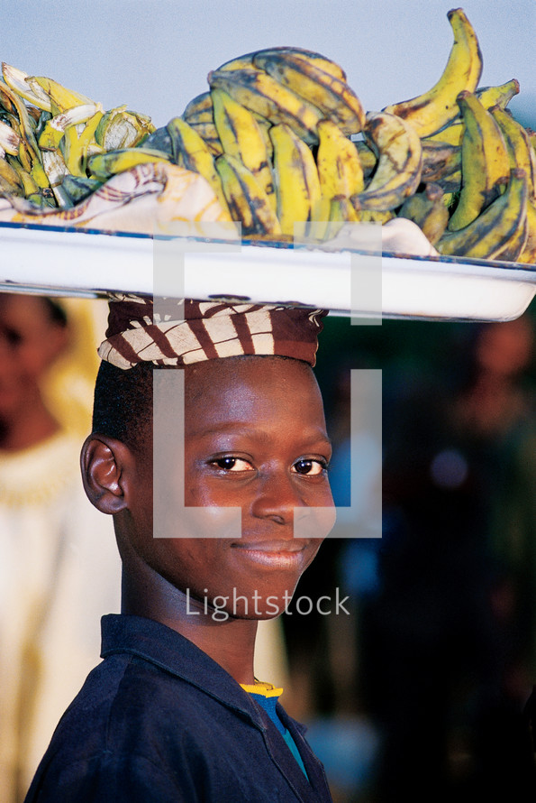 A smiling boy carrying a plate of bananas on his head.