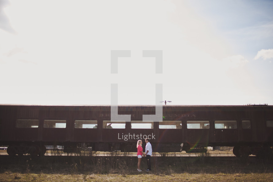 man and woman holding hands standing in front of an old railway car