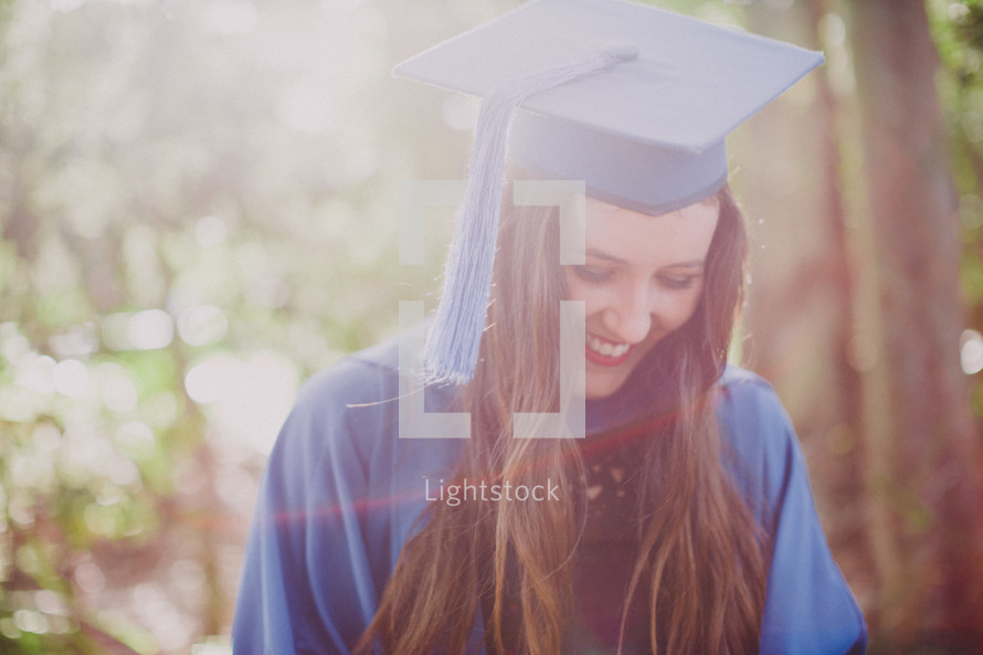 Woman in her cap and gown at graduation under sunlight