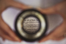 "Hands holding magnifying glass over ""The Wife of Noble Character"" scripture."