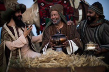 wisemen traveling on camels presenting gifts to baby Jesus