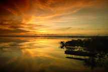 The sun rises over the Amazon river with a local's boat docked in the foreground.