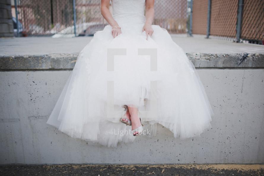 Bride sitting on a curb