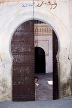Child peeking through an ornate doorway