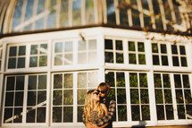 couple in an embrace standing outdoors in front of windows