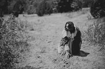 Jesus kneeling in the wilderness
