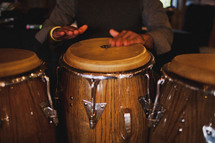 Hands beating on bongo drums in dimly-lit room.