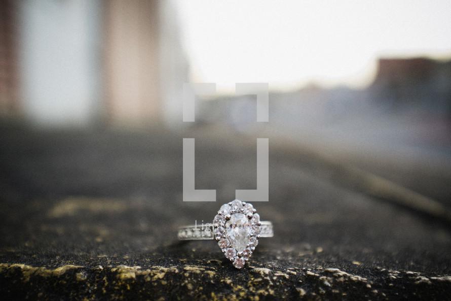 engagement ring on asphalt