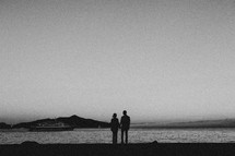 Couple holding hands by the water