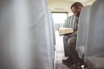 a man reading a Bible on a church bus
