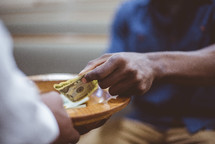 man putting money in an offering plate