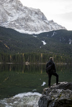 a man standing on a rock by a mountain lake