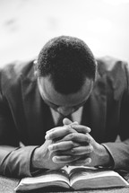 a man praying over a Bible in a church