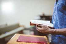 a man reading from a Bible during a worship service