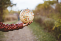 outstretched arm with a globe