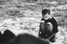 a squatting boy playing in dirt
