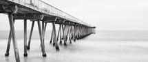 a pier extending into a calm ocean