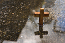 wooden cross in a puddle