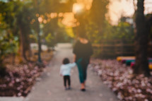 a mother and daughter walking on a sidewalk holding hands
