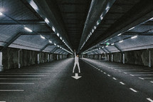 man with a raised arm standing in a parking garage