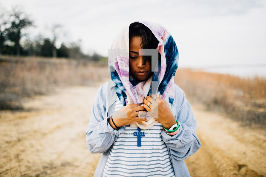 African American woman standing on a dirt road with a scarf over her head