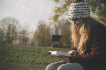 a teen girl reading a Bible on a bench outdoors