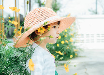 a little girl in a sunhat standing next to flowers