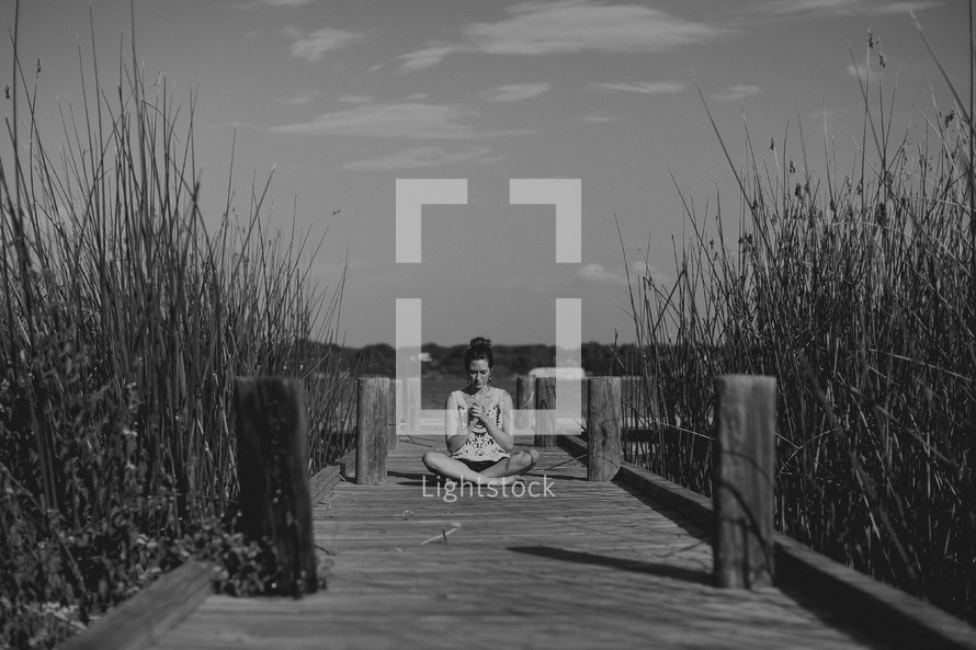 girl praying on a pier