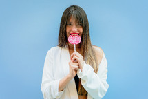 a woman biting a lollipop