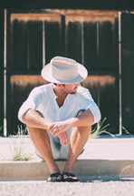 a man sitting on the curb in a cowboy hat and flip flops