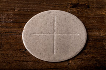A communion wafer on a wooden surface.