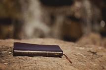 Bible lying on top of rock.