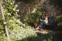 Woman sitting on bench in garden reading the bible.