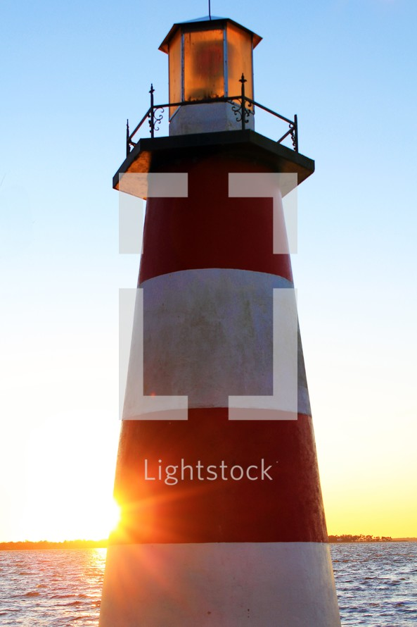 A  lighthouse with red and white stripes stands over an inlet of water and land as the sun sets behind it casting a ray of yellow and gold light against the sky and horizon.