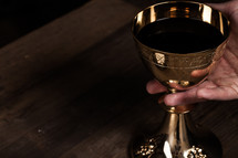 A hand lifting a golden wine goblet.