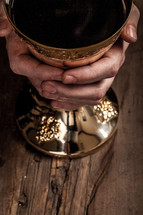 Hands holding a golden goblet of wine on a wooden surface.