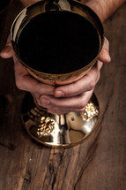 Hands grasping a golden goblet of communion wine.