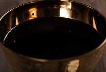 A golden goblet full of wine.
