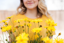 a woman standing behind yellow flowers
