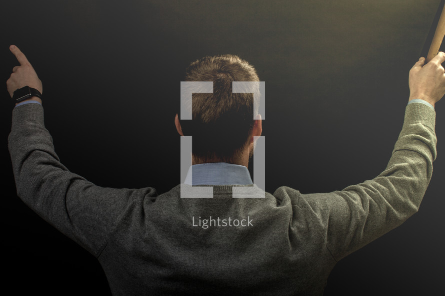 Light shining on the back of a man who is preaching.
