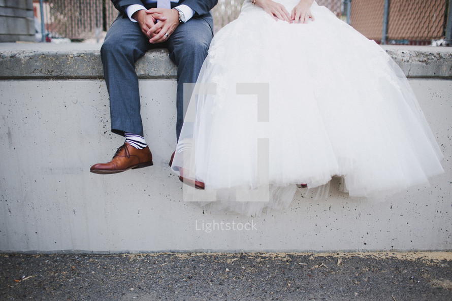 legs of a bride and groom dangling while sitting on a concrete wall