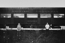 man and woman standing in front of an old railway car