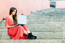 young woman sitting on outdoors stairs wearing red dress with a computer