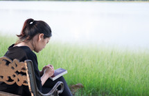a woman praying outdoors on a park bench
