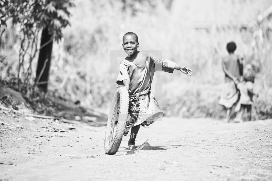 A young boy running and playing with a tire.