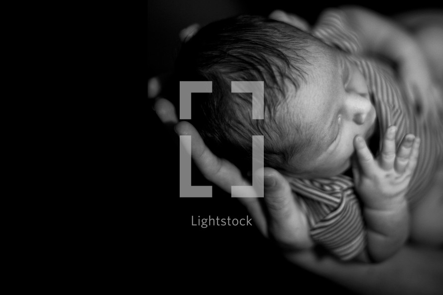 hands holding a sleeping newborn baby