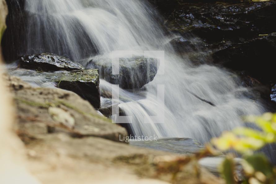 Waterfall in rock-lined stream.